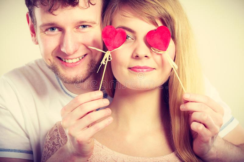 Couple blinded by their love. Love and happiness concept. Cheerful enjoyable young couple with little small hearts on sticks covering women men eyes. Lovers stock photography