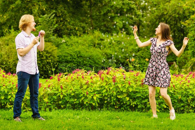 Couple blowing bubbles outdoor royalty free stock image