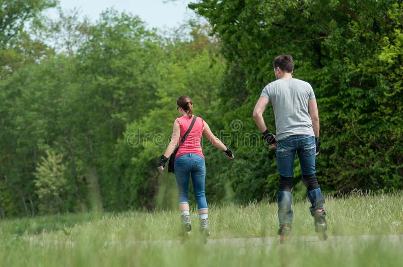 Couple in blue jeans drives roller skates in border forest. Mulhouse - France - 29 April 2018 - couple in blue jeans drives roller skates in border forest royalty free stock photography