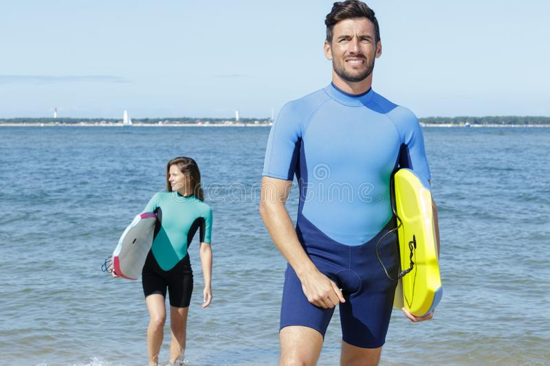 Couple body boarders getting out sea. Couple of body boarders getting out of the sea stock images