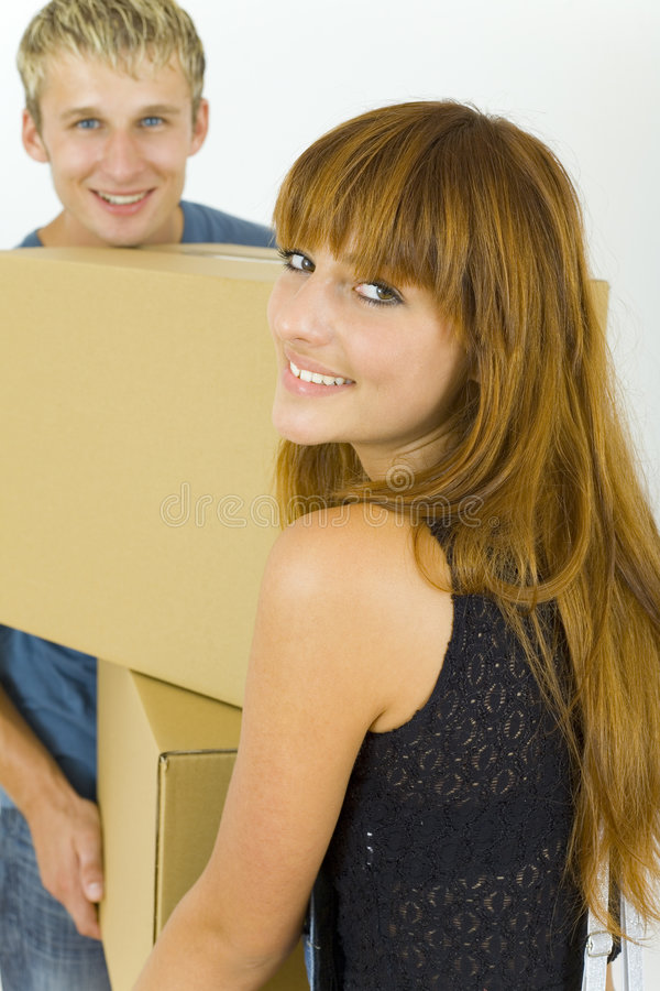Couple with box. Young, smiling couple standing and holding box. They're looking at camera. Gray background royalty free stock photos