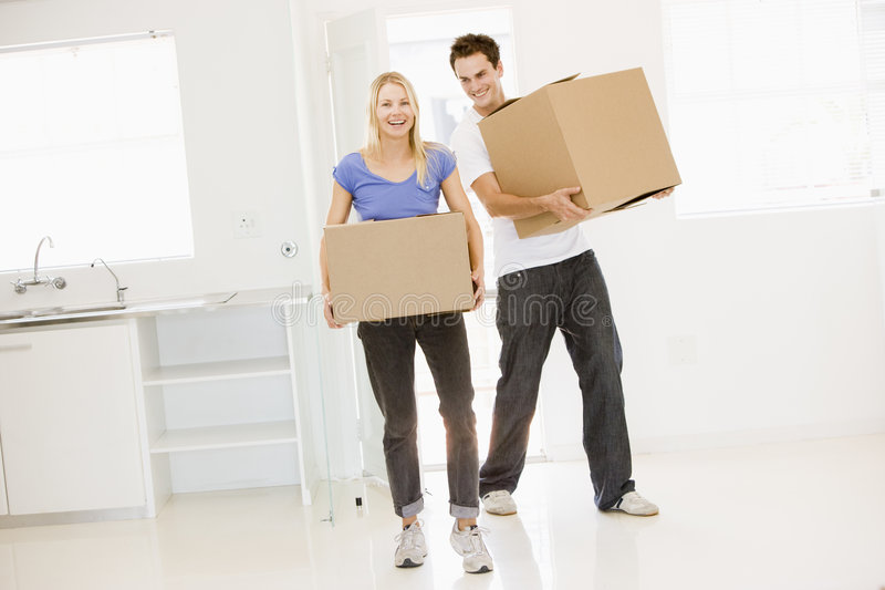 Couple with boxes moving into new home smiling royalty free stock image
