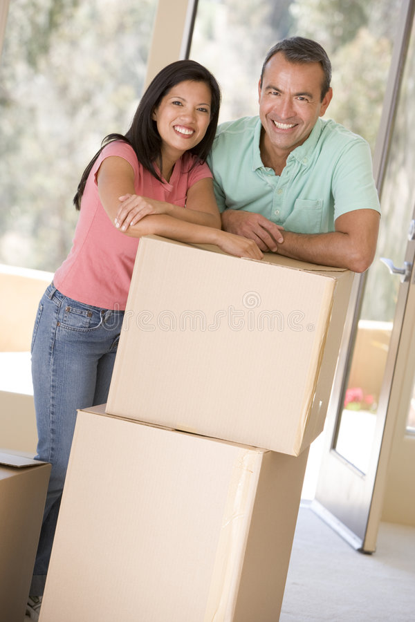 Couple with boxes in new home smiling stock photography