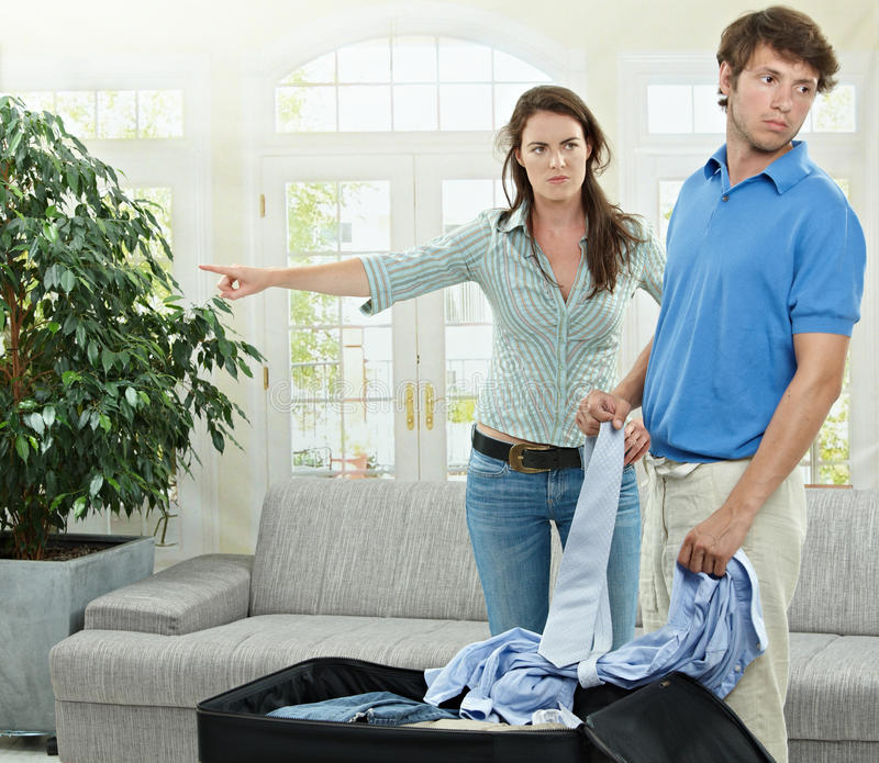 Couple braking. Unhappy couple breaking. Angry woman pointing out, man packing his clothes into suitcase