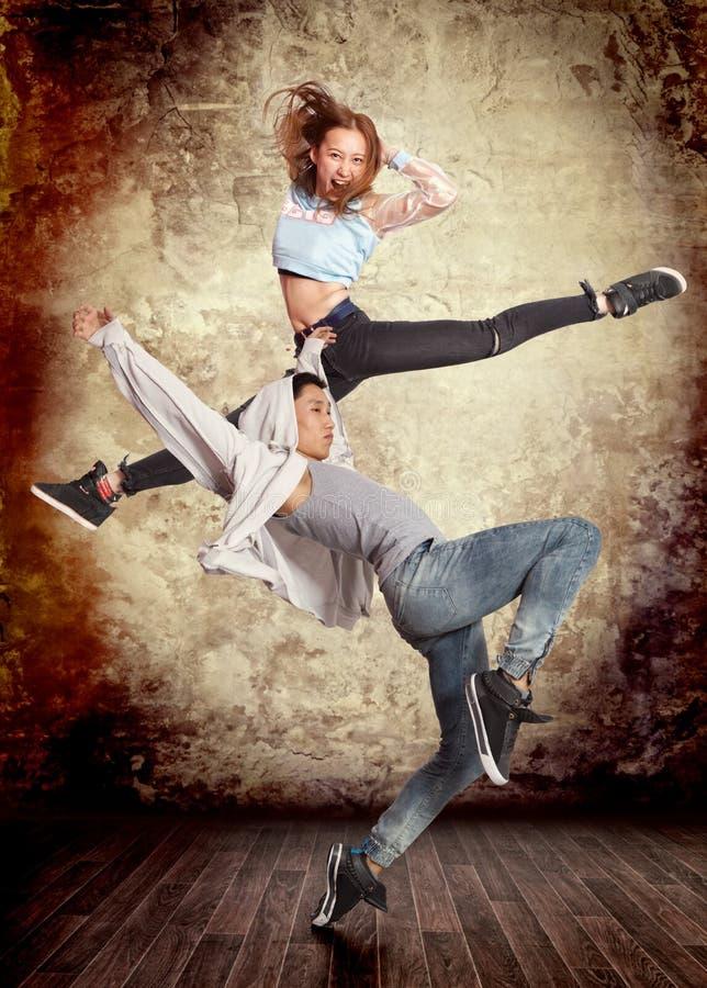 Couple break dancing on wall background stock image