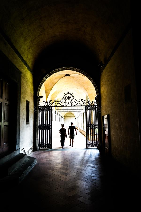 Couple in breezeway, Florence, Italy. Couple walking through outdoor breezeway in Florence, Italy on sunny day royalty free stock photo