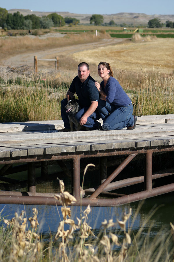 Couple on Bridge. A man and woman couple in the country, with their dog. The couple is situated on a bridge as water flows underneath royalty free stock photography