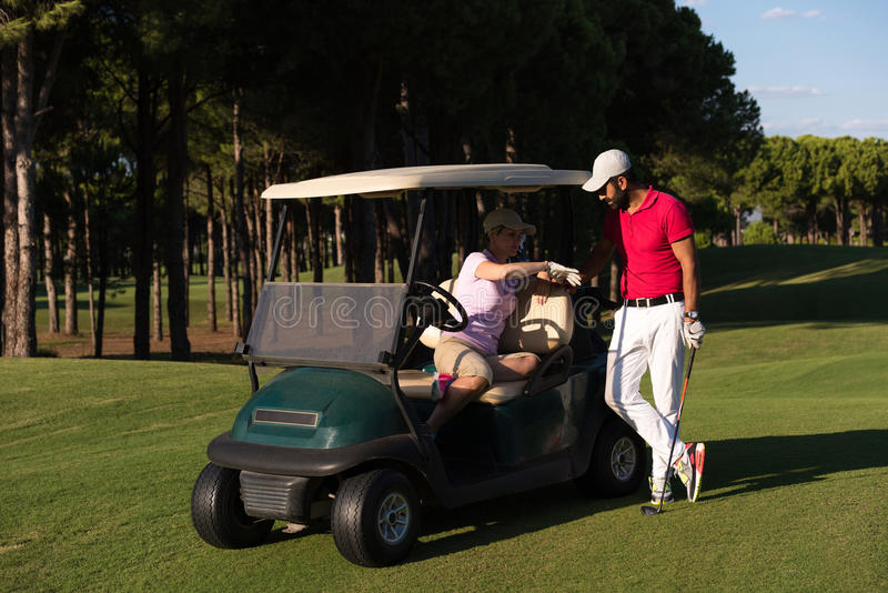 Couple in buggy on golf course. Couple in buggy cart on golf course stock images