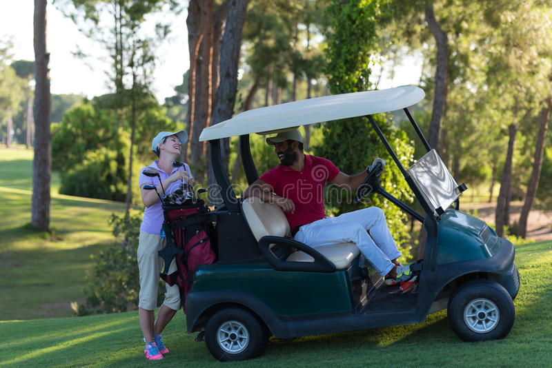 Couple in buggy on golf course. Couple in buggy cart on golf course royalty free stock photo
