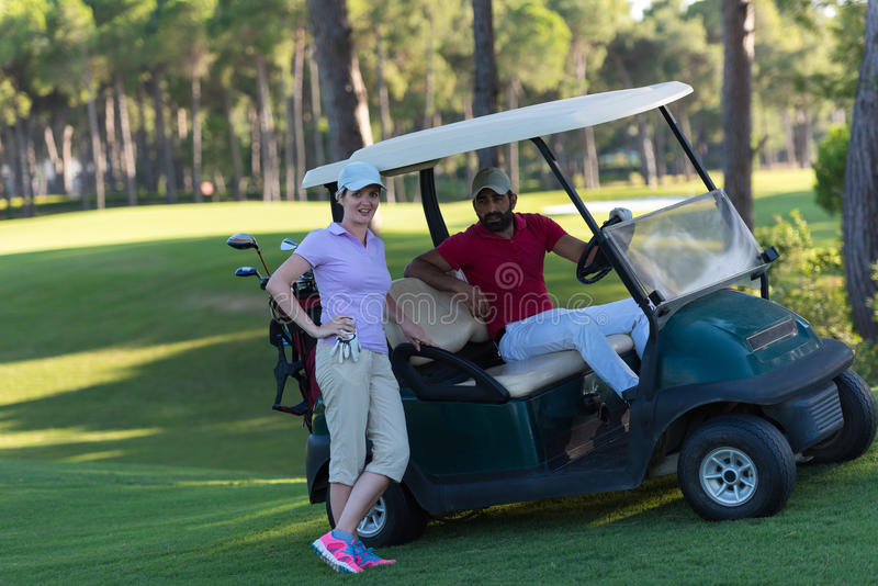 Couple in buggy on golf course. Couple in buggy cart on golf course royalty free stock image