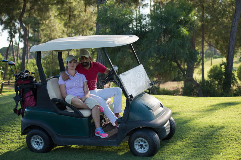 Couple in buggy on golf course. Couple in buggy cart on golf course royalty free stock images