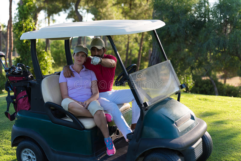 Couple in buggy on golf course. Couple in buggy cart on golf course royalty free stock photos
