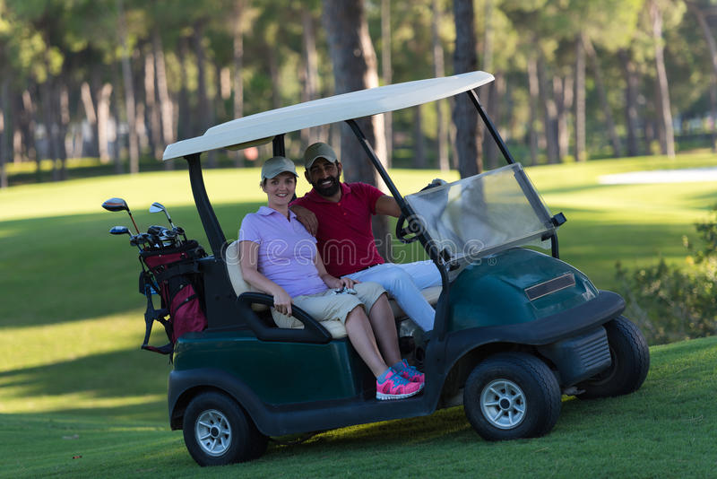 Couple in buggy on golf course. Couple in buggy cart on golf course stock photos