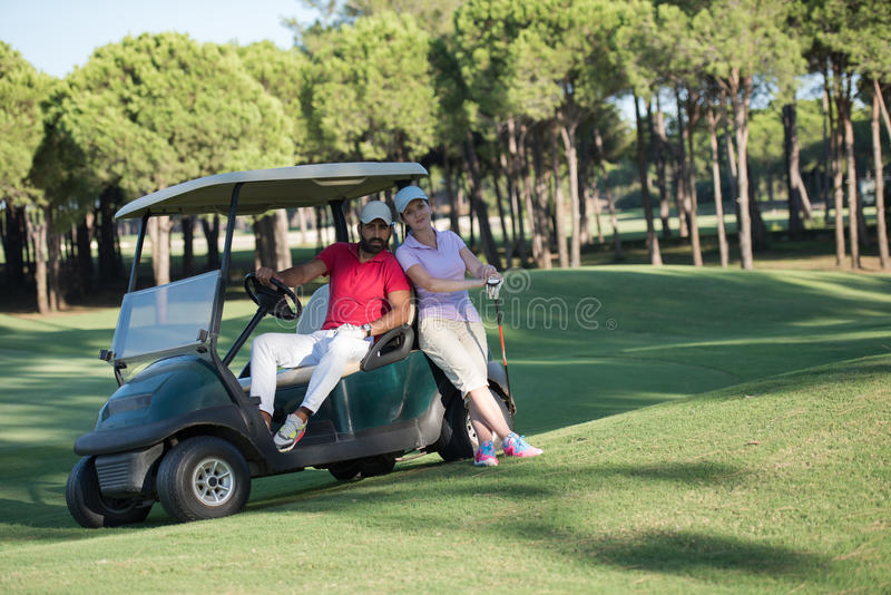 Couple in buggy on golf course. Couple in buggy cart on golf course stock photo