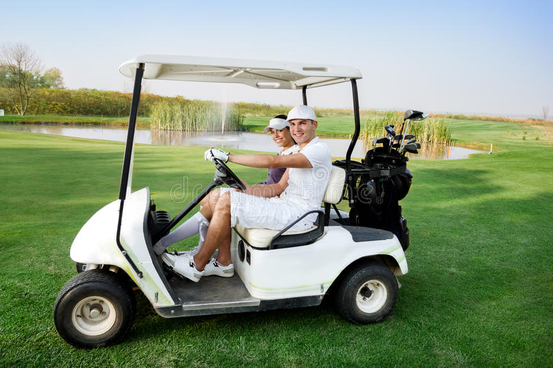 Couple in buggy in golf course. Couple in driving buggy on golf course stock image