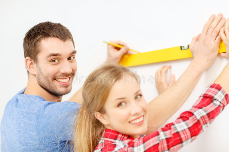 Couple building using spirit level to measure. Repair, building and home concept - smiling couple building new home using spirit level to measure royalty free stock image