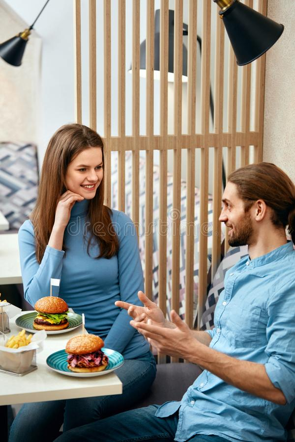 Couple With Burgers In Cafe royalty free stock image