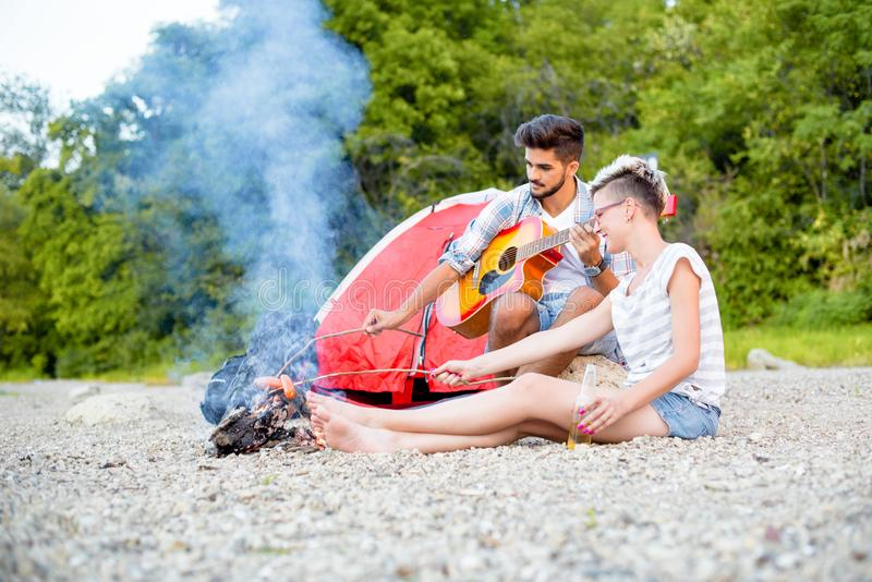 Couple burning sausages at campfire. On beach royalty free stock image