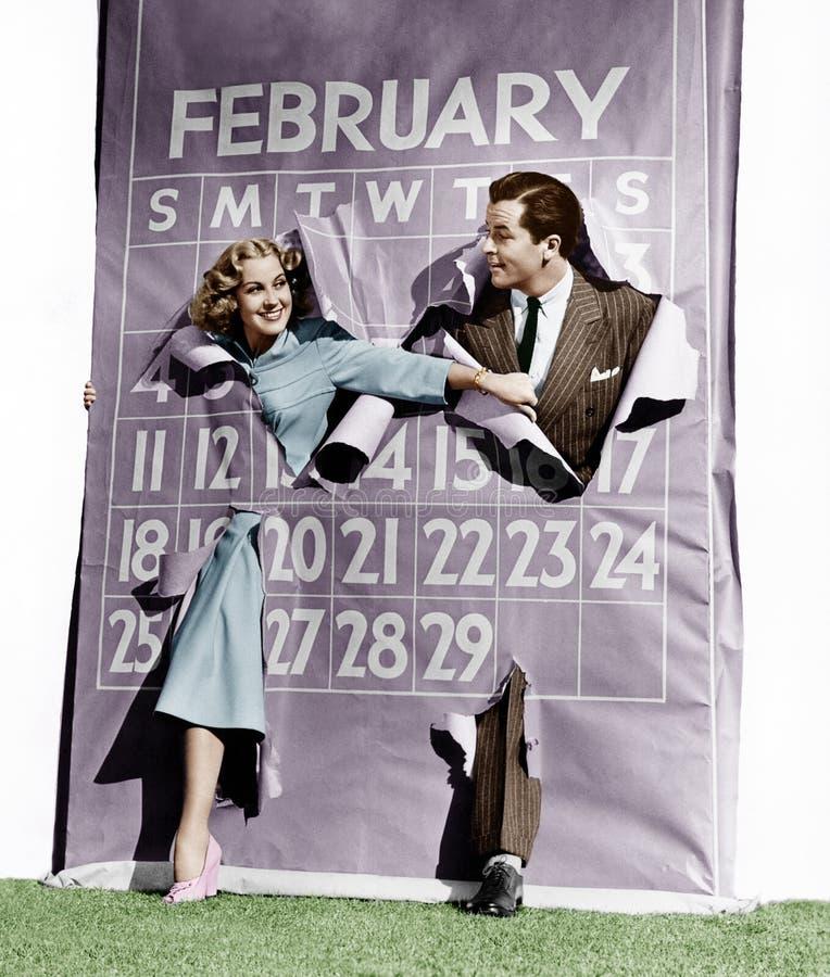 Couple bursting through leap year calendar royalty free stock image