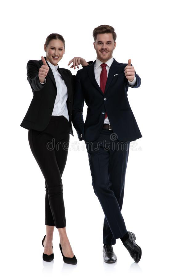 Couple in business suits liking with thumbs up. Couple in business suits standing with legs crossed and thumbs up liking on white background stock images