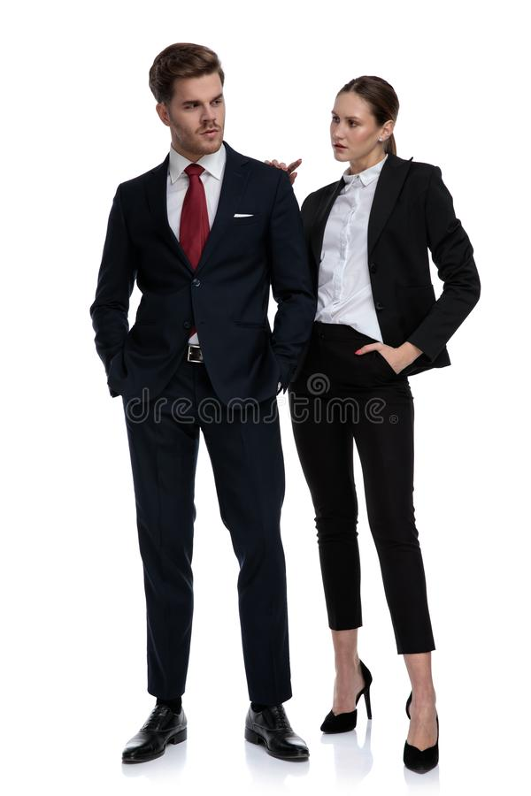 Couple in business suits looking serious stock image