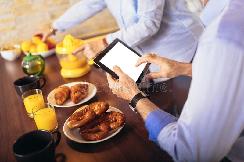 Couple busy look at digital tablet while having delicious breakfast at home kitchen royalty free stock photo