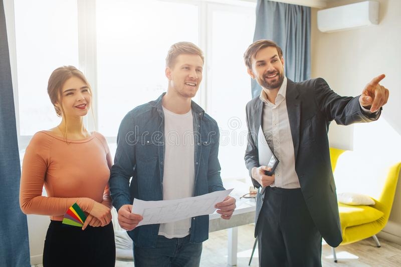 Couple buy or rent apartment together. Business deal and talk. Realtor point forward. Happy positive clients. They all royalty free stock image
