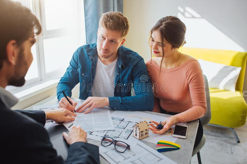 Couple buy or rent apartment together. Business deal. Young man put signature on documents and look at realtor. He point royalty free stock photography
