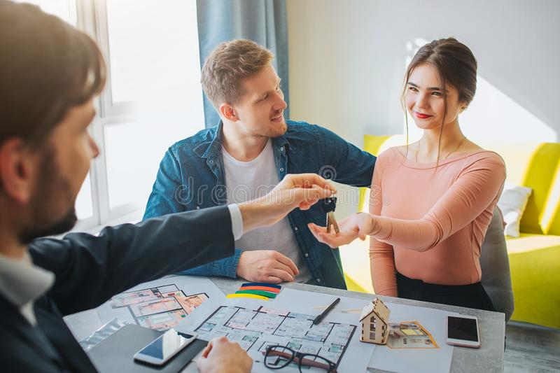 Couple buy or rent apartment together. Cheerful delightful young woman reach hand and get keys from realtor. Man look at stock photo
