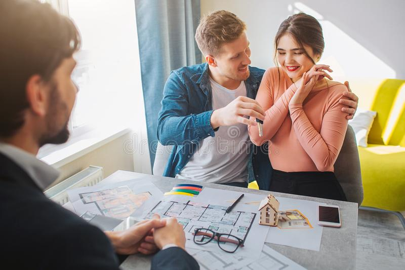 Couple buy or rent apartment together. Happy young woman get keys from man. He embrace her. Reltor sit in front of them. Couple buy or rent apartment together royalty free stock photo