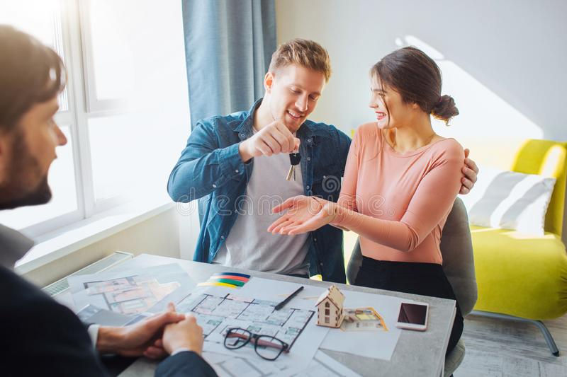 Couple buy or rent apartment together. Happy young woman get keys from man. Realtor sit in front of them. Apartment plan royalty free stock images