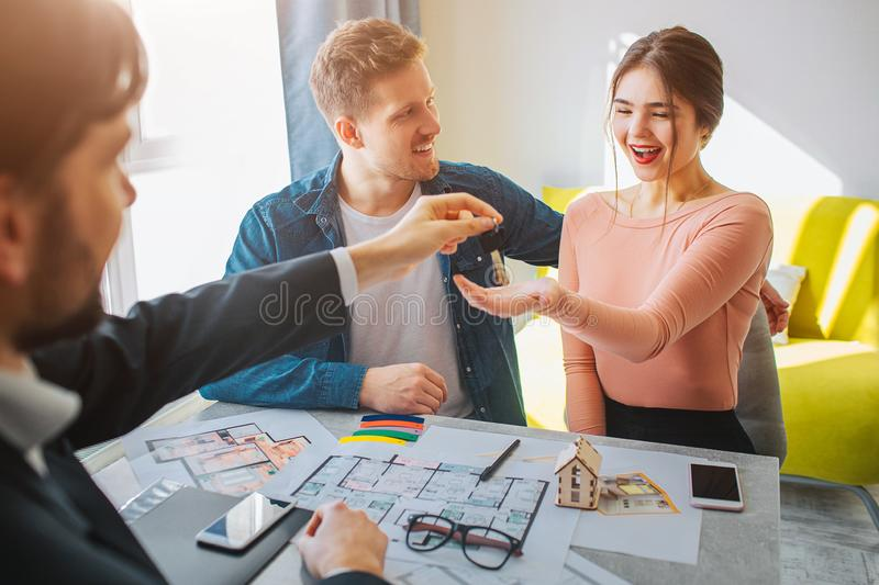 Couple buy or rent apartment together. Happy young woman reach hand and get keys from realtor. Man look at her and smile royalty free stock photo