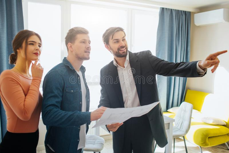 Couple buy or rent apartment together. Realtor point forward. Couple look at that way. Positive and thoughtful. Business stock images