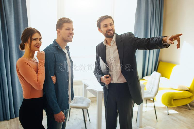 Couple buy or rent apartment together. Realtor point forward. Young couple look in that way and smile. Woman stand. Behind man. Happy royalty free stock image