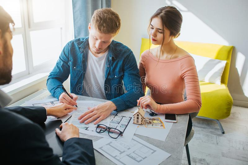 Couple buy or rent apartment together. Serious concentrated man put signature on documents. Business deal. Young woman stock image