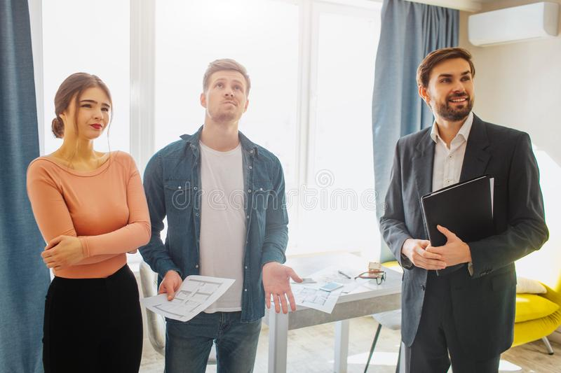 Couple buy or rent apartment together. They stand with realtor. Young man look up. Woman has doubts. Cheerful realtor. Look rorward royalty free stock photo