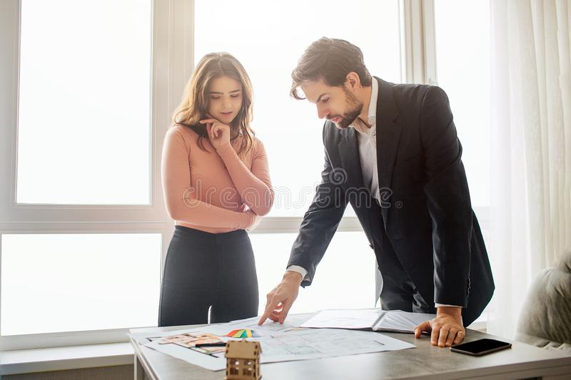 Couple buy or rent apartment together. They stand upon table and hold there plan. Young man look at it. He lean to table stock photography
