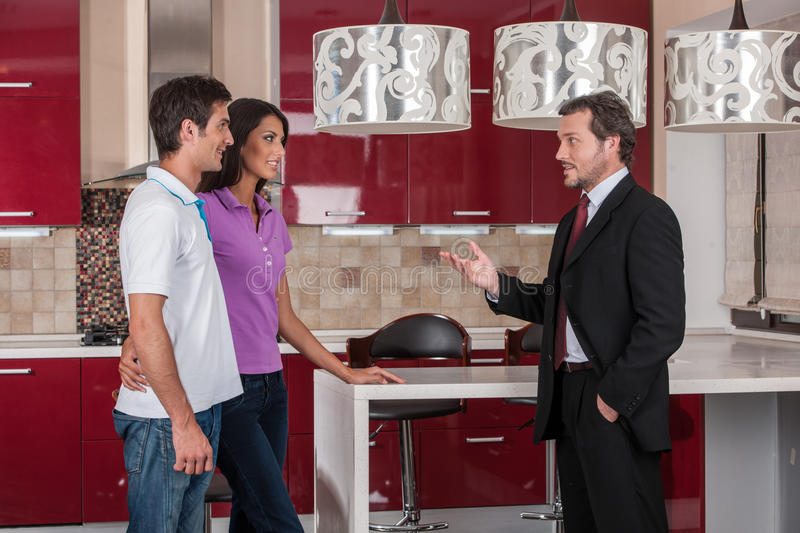 Couple of buyers visiting new house. Young couple choosing new kitchen royalty free stock image