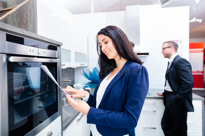 Couple buying domestic kitchen in furniture store. Woman picking oven for domestic kitchen in studio or furniture store royalty free stock image