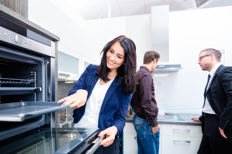 Couple buying domestic kitchen in furniture store. Woman picking oven for domestic kitchen in studio or furniture store royalty free stock photos