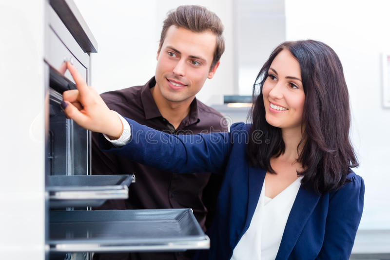 Couple buying domestic kitchen in furniture store. Woman picking oven for domestic kitchen in studio or furniture store showroom stock images