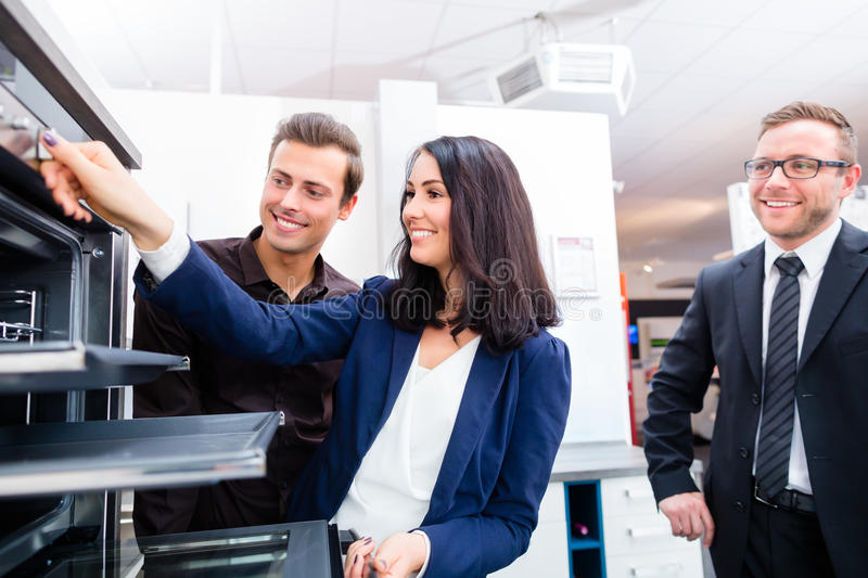 Couple buying domestic kitchen in furniture store. Woman picking oven for domestic kitchen in studio or furniture store showroom royalty free stock images