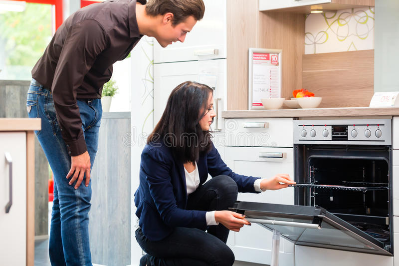 Couple buying domestic kitchen in showroom. Man and women buying domestic kitchen in studio or furniture store showroom stock photo