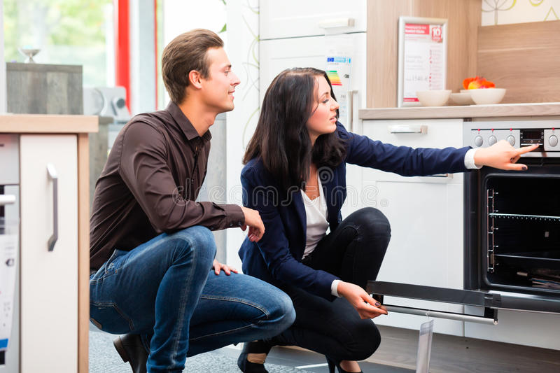 Couple buying domestic kitchen in showroom. Man and women buying domestic kitchen in studio or furniture store showroom stock photos