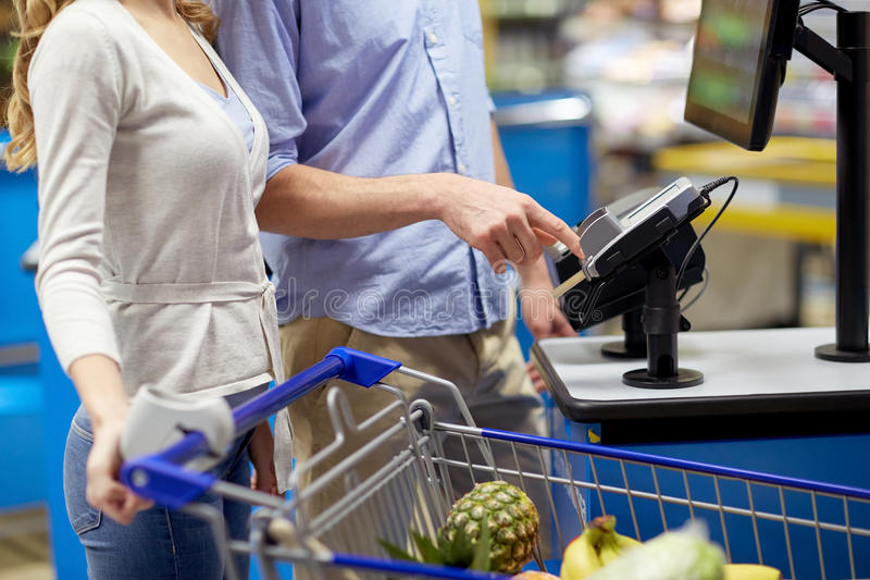 Couple buying food at grocery self-checkout stock image