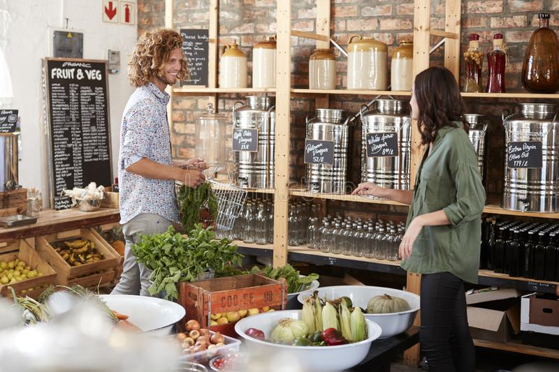 Couple Buying Fresh Fruit And Vegetables In Sustainable Plastic Free Grocery Store royalty free stock images