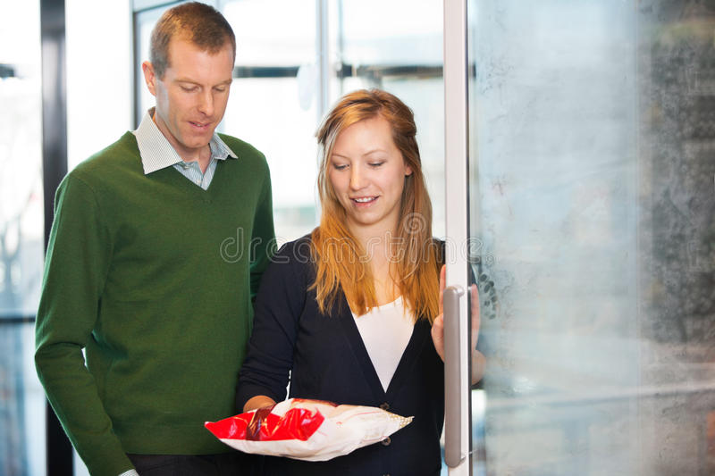 Couple Buying Frozen Food. Woman taking out product from freezer while shopping with husband royalty free stock photo
