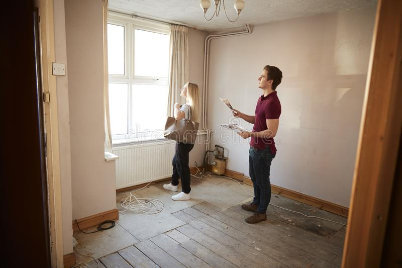 Couple Buying House For First Time Looking At House Survey In Room To Be Renovated royalty free stock photography