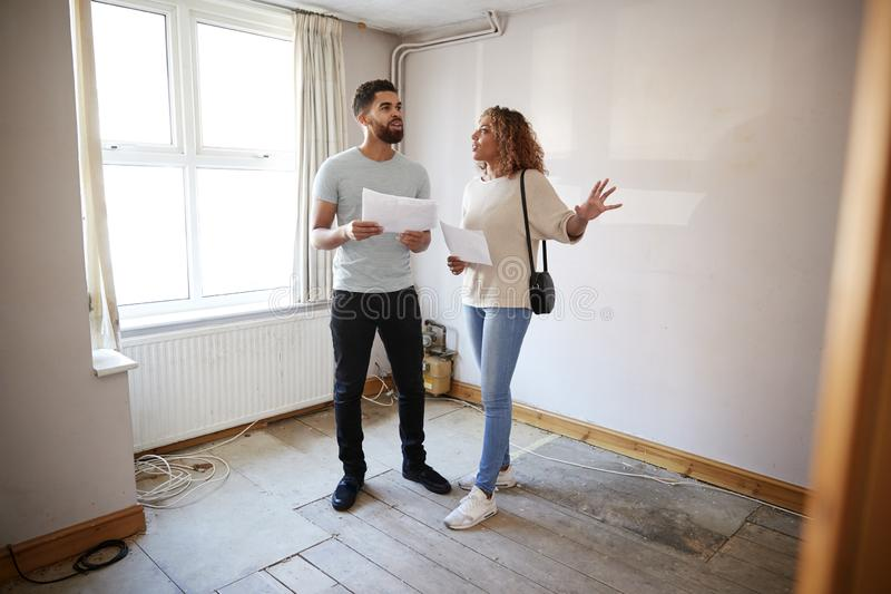 Couple Buying House For First Time Looking At House Survey In Room To Be Renovated royalty free stock photo