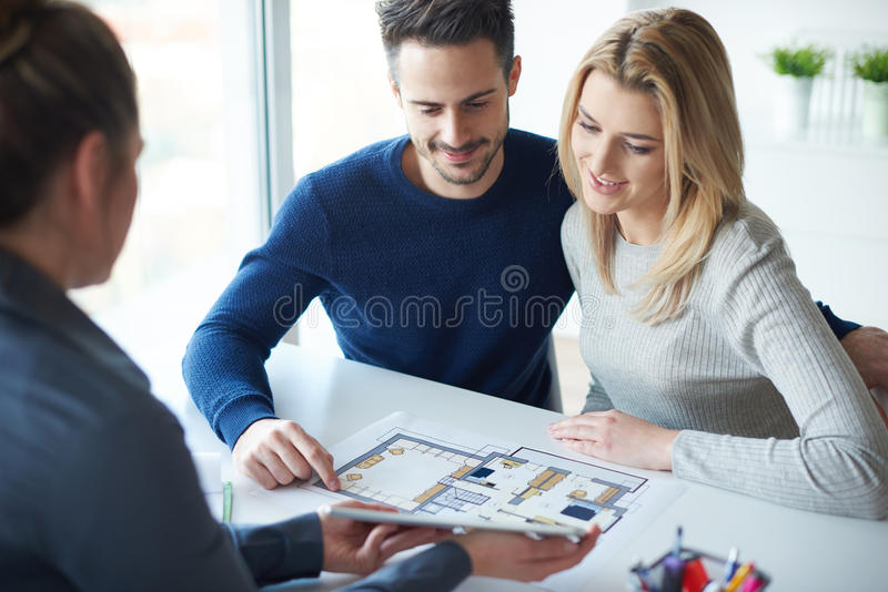 Couple buying noew home. Saleswoman showing paperwork to couple royalty free stock photography
